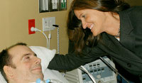 Woman leaning over man in hospital bed